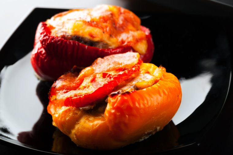 Stuffed bell peppers with chopped meat, cheese and tomato lay on black plate